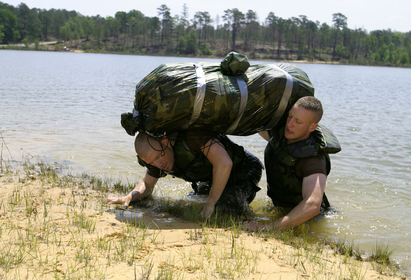 USA Army Rangers Robert Ossman (L) and Eric Buonopane (R) lift their gear to shore during the Helo Cast.