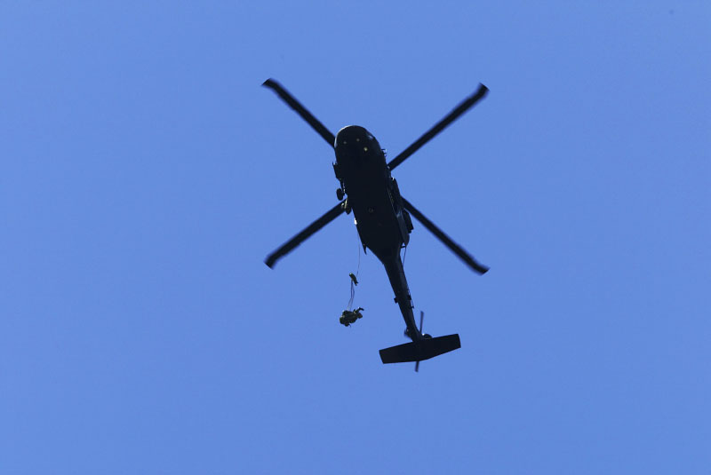 Rangers jump from a helicopter during the spot jump competition.