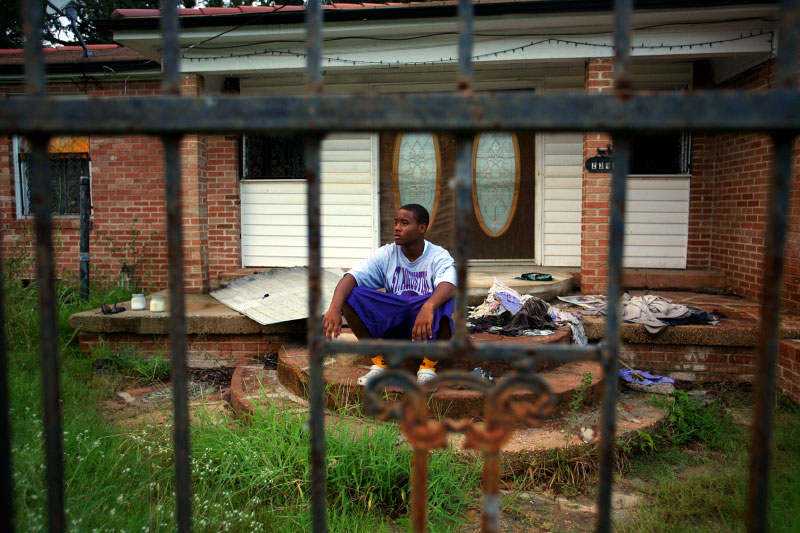 St. Augustine freshman long snapper Rodney Mitchell sits on front steps of his abandoned home which was destroyed by Katrina.