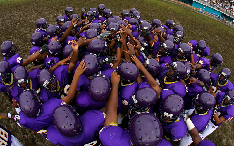 The Purple Knights meet at mid-field just prior to the kickoff. Heavy rain fell in the morning and left the field muddy.
