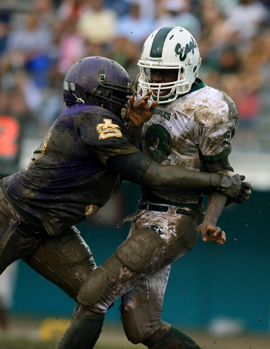 A Purple Knight defensive player makes a play against the Shaw quarterback.
