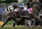The Purple Knights defense stops a Shaw runner in the mud.