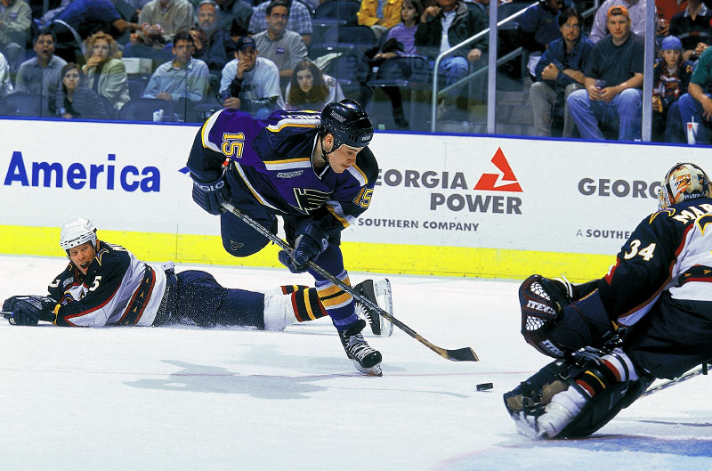 St. Louis Blues center Marty Reasoner bears in on Atlanta Thrashers goalie Norm Maracle as Thrashers defenseman Gord Murphy watches from a prone position on the ice