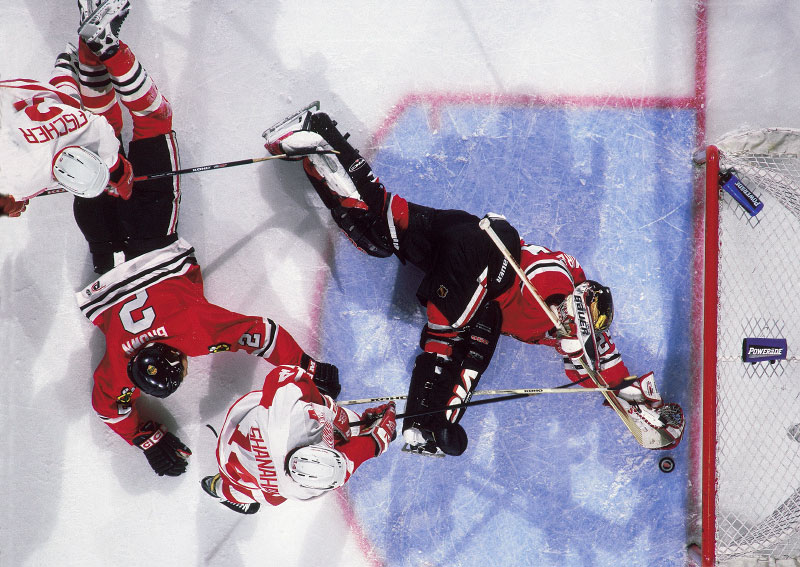 Chicago Blackhawks goalie Steve Passmore makes a sprawling save on a shot by Detroit Red Wings Brendan Shanahan. Blackhawks defenseman Brad Brown dives at the top of the crease in an attempt to break up the play