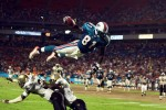 Miami Dolphins tight end Randy McMichael leaps over two New Orleans Saints defenders to score a touchdown.