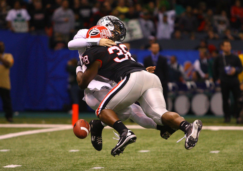 Georgia Bulldogs defensive end Marcus Howard sacks Hawaii Warriors quarterback Colt Brennan causing a fumble in the 2008 Sugar Bowl. The fumble resulted in a Georgia touchdown.