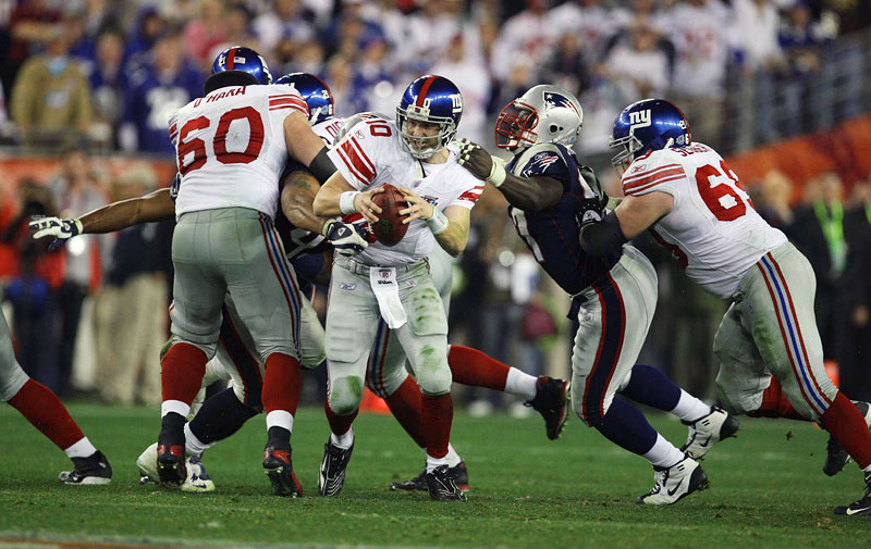 New York Giants Eli Manning escapes a sack late in the game to make a throw to David Tyree that set up the winning touchdown in Super Bowl XLII against the New England Patriots