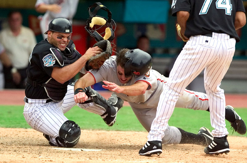 San Francisco Giants JT Snow slams into Florida Marlins catcher Ivan Rodriguez as he holds onto the ball for the final out of game and series