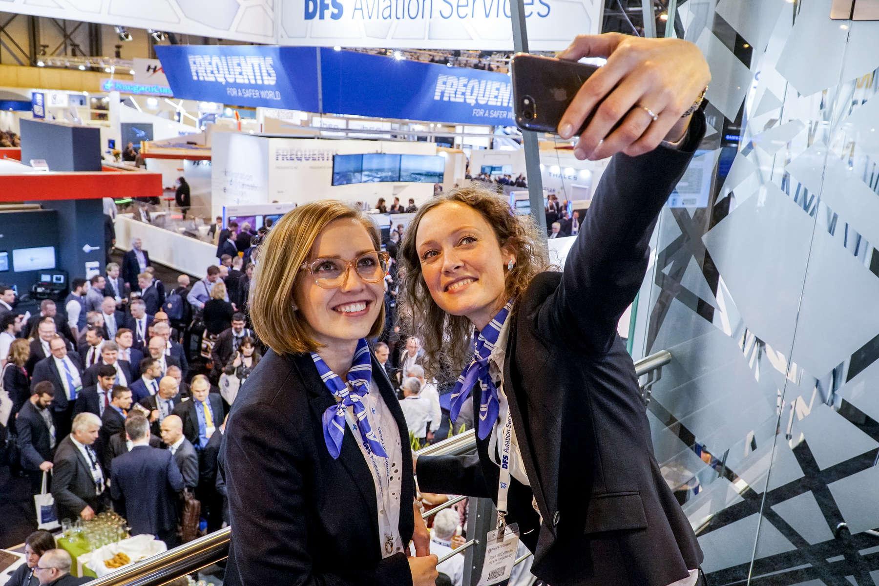 Carolin Walaski and Irina Woehrmann take a selfie at the DFS Aviation Services booth reception.