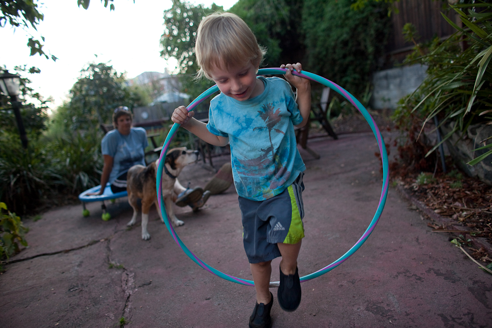 3 year old Wade Baer-Bukowski plays in his backyard as his mom Lois Bukowski and their dog Jackson looks on.