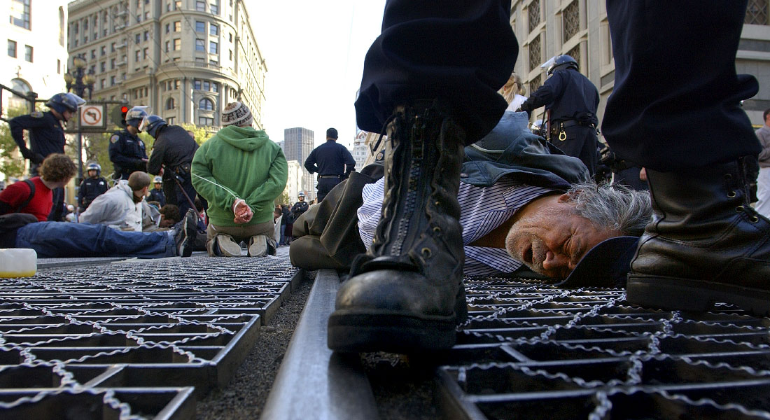 A man lies face down on Market Street as he gets arrested for taking part in a anti-war protest.