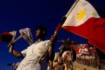 A man sells national flags in front of a statue of Andrés Bonifacio y de Castro.