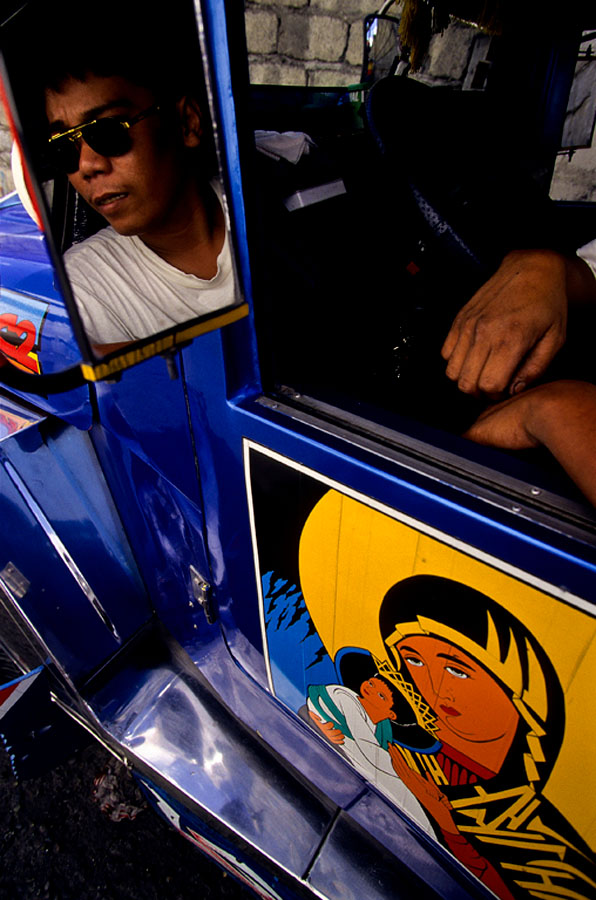 A taxi driver sits in his Jeepnee as he waits for riders in Manila, Philippines.
