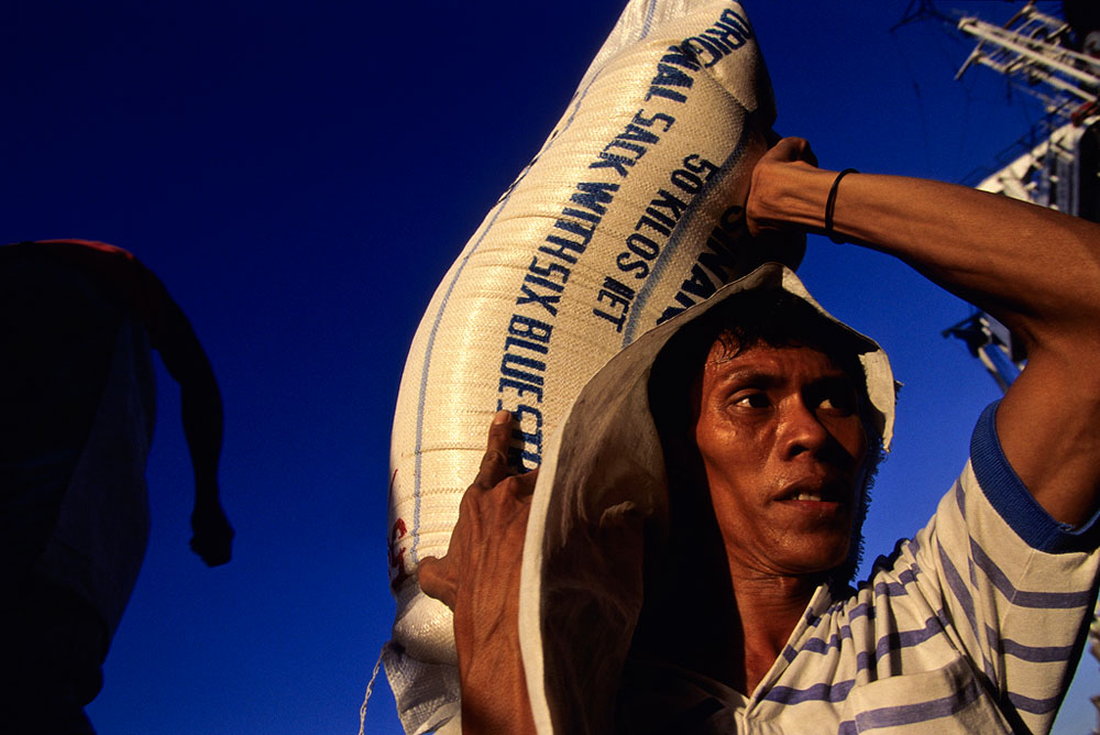 A worker on the docks in the port of Manila unloads 50KG sacks of rice.