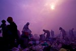 Working in hazy and smokey skies workers look through trash for recyclable materials. Much of the trash is burned in the same areas where people are working putting out toxic smoke.