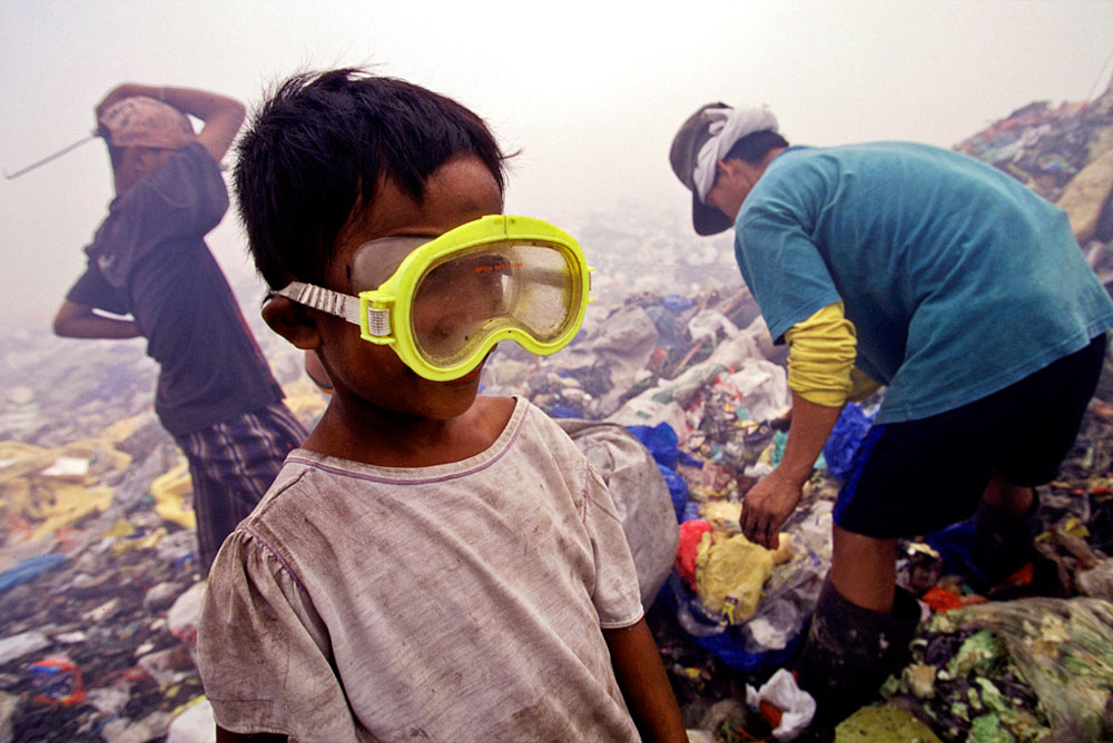 A boy uses swim goggles to protect his eys from the burning smoke in the air.