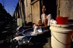 A woman washes her dishes outside her home in Manila, Philippines.