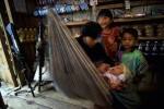 A woman shopkeeper tends to her baby as her other children look on in a Abu Sayyaf camp on the muslim island of Mindanao, Philippines.