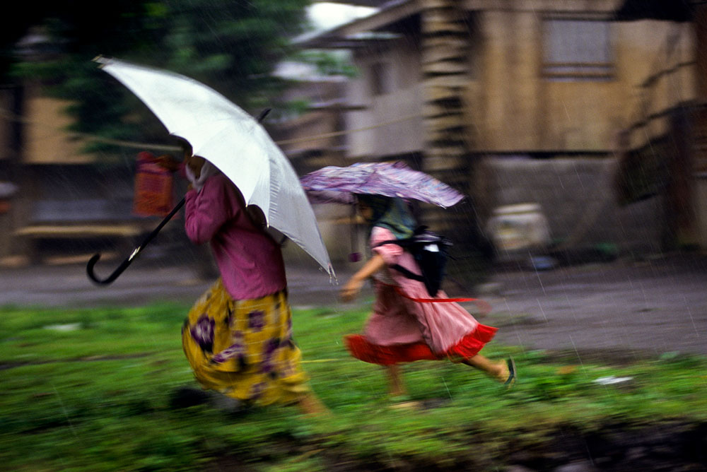 Two young girls run in the rain at a Abu Sayyaf camp on the muslim island of Mindanao, Philippines.