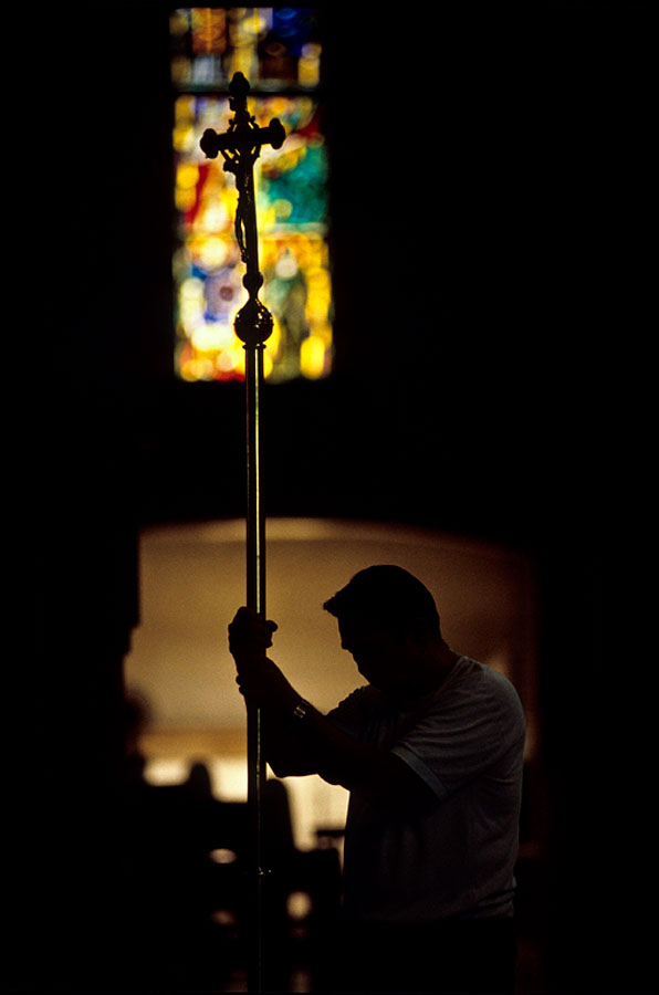 A man holds a cross as he goes through the stations of the cross in a church in Manila, Philippines.