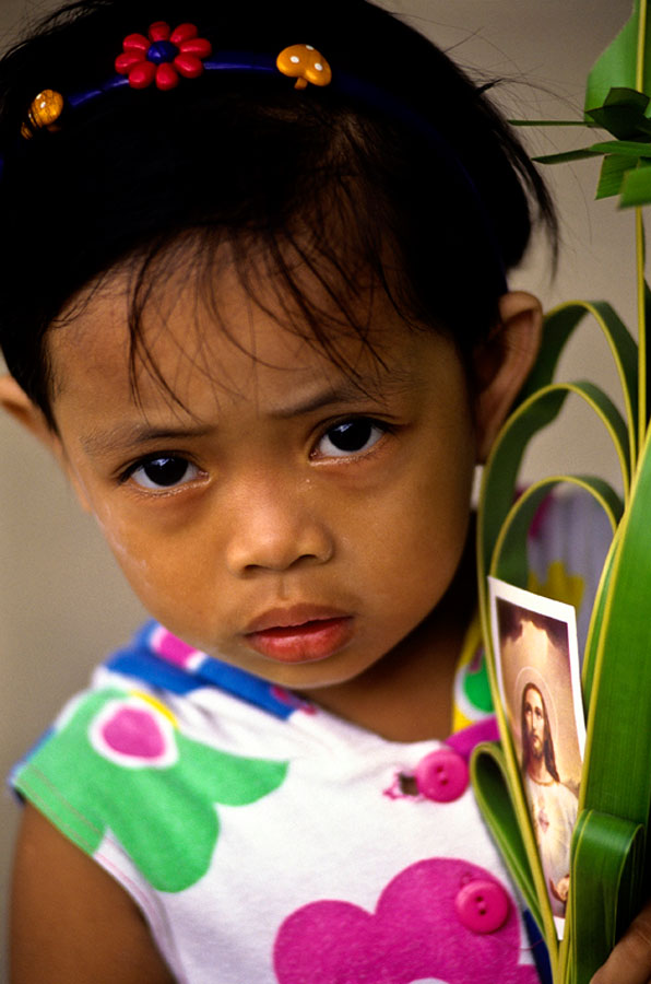 A young girl carries a palm with a photo of Jesus as she celebrates Palm Sunday in Manila, Philippines.