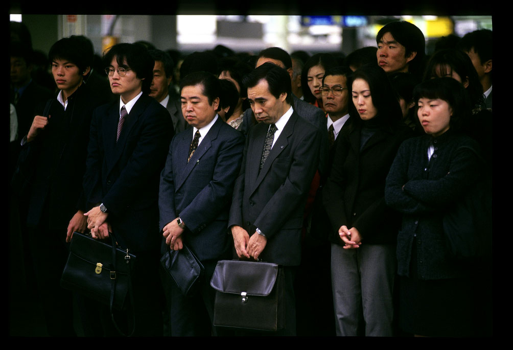 People wait for the train during the early morning hours in Tokyo, Japan.