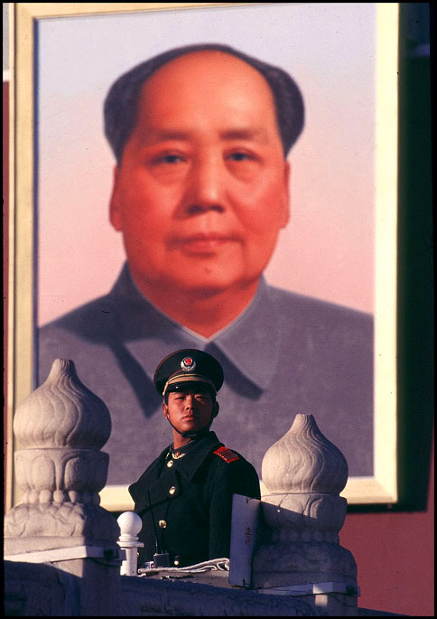 Under the watchful eye of a portrait of Mao Zedong, a PLA soldier stands guard at the entrance of the Forbidden City in Beijing, China.