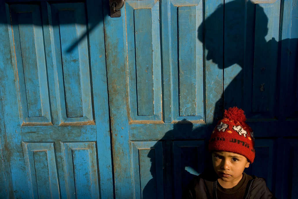 A young boy stands against a door on a street in Kathmandu, Nepal.