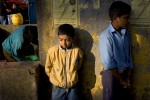 Two young boys stand against a wall as a women washes clothes on a street in Kathmandu, Nepal.