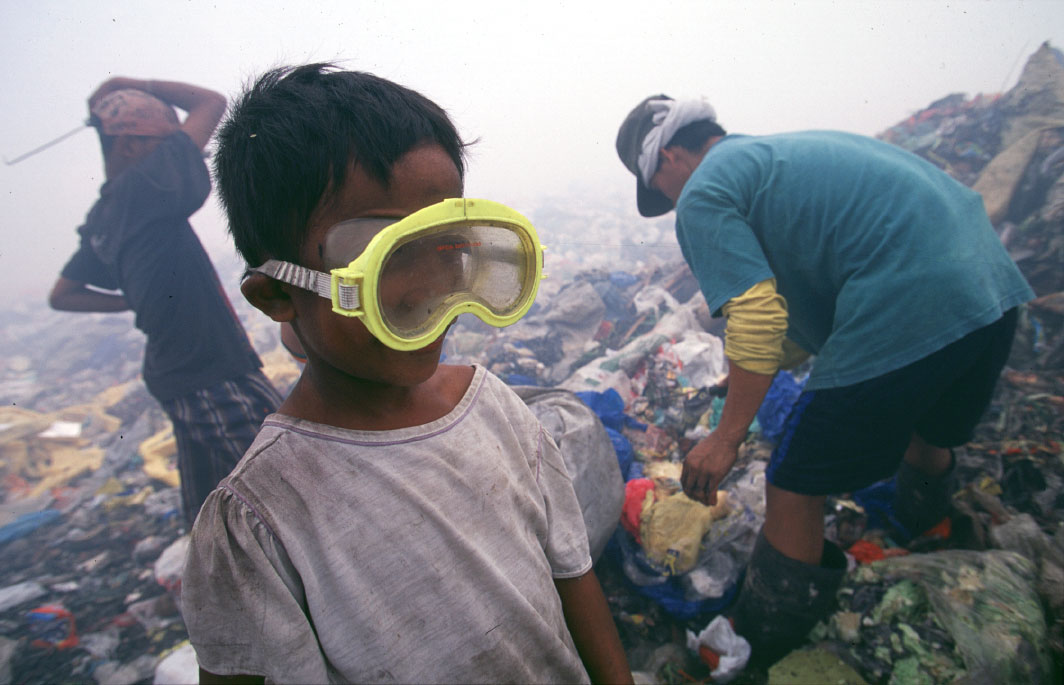 A young boy uses a swim mask to protect his eyes from the burning smoke while working at the Payatas. Much of the trash is burned in the same areas where people are working putting out toxic smoke.