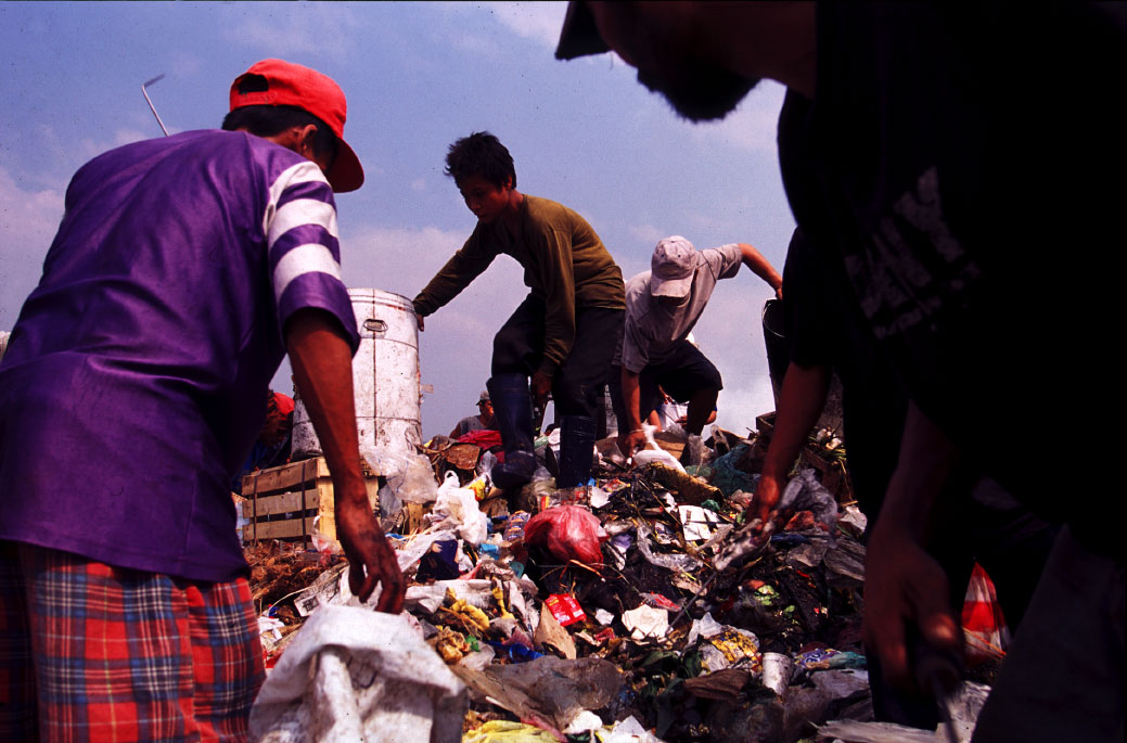 Workers climb over mountains of trash as they look for recyclable goods.