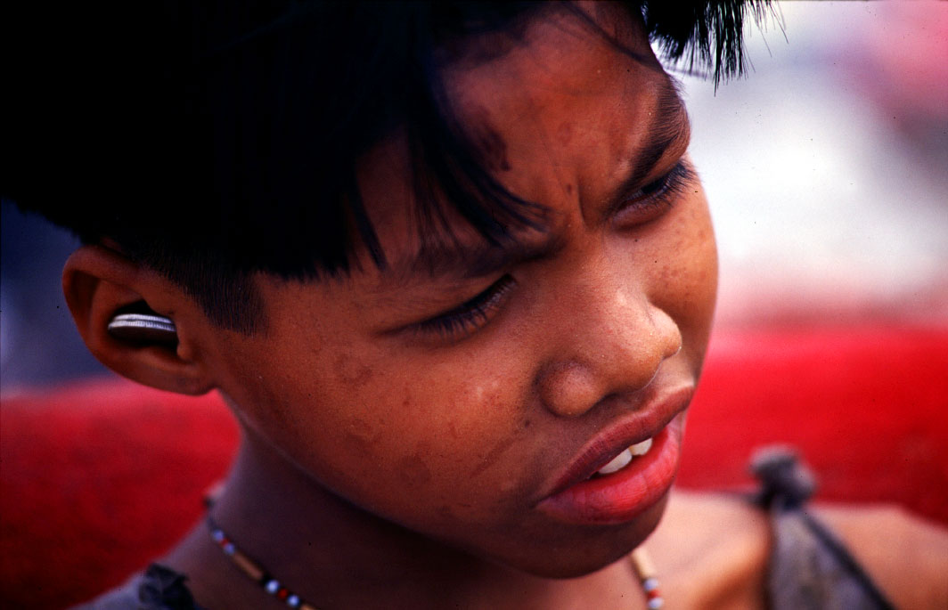 A young boy with coins in his ears takes a break from working at Payatas.