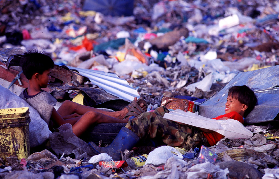 Two young boys sit in the trash as they take a break from working at the Payatas.