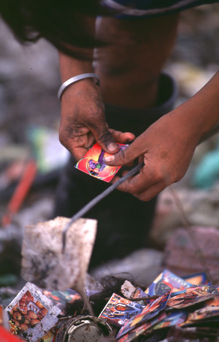 A young boy looks through some playing cards he fournd while working at the Payatas.