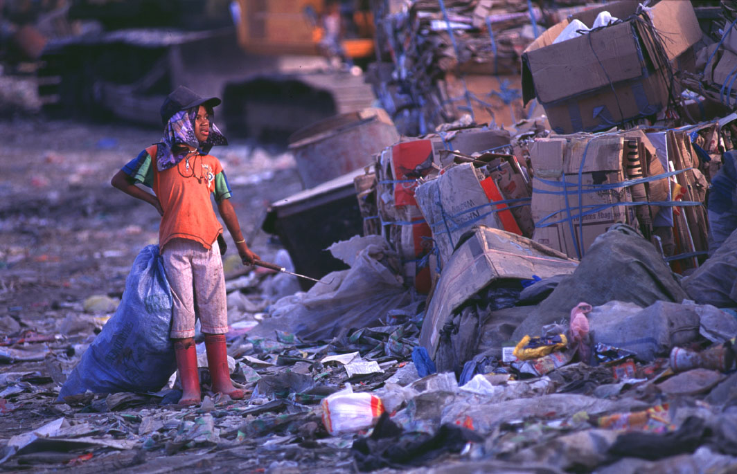 A young girl looks over a mountain of trash before starting her dailywork at the Payatas.