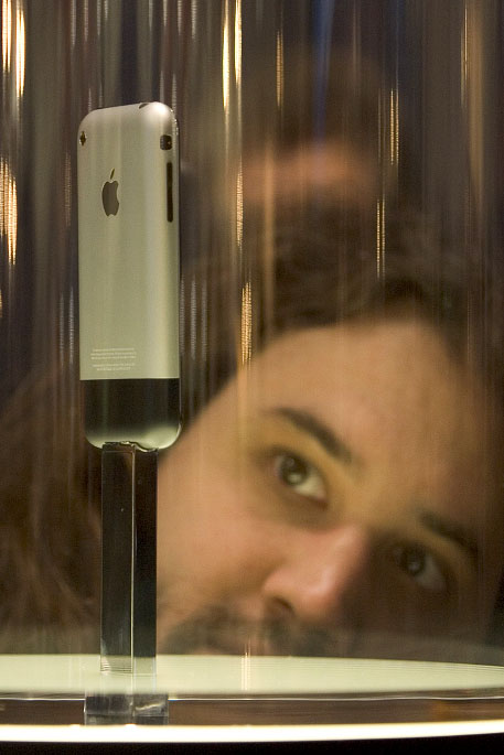A man looks over the new iPhone that was on display during MacWorld 2007.