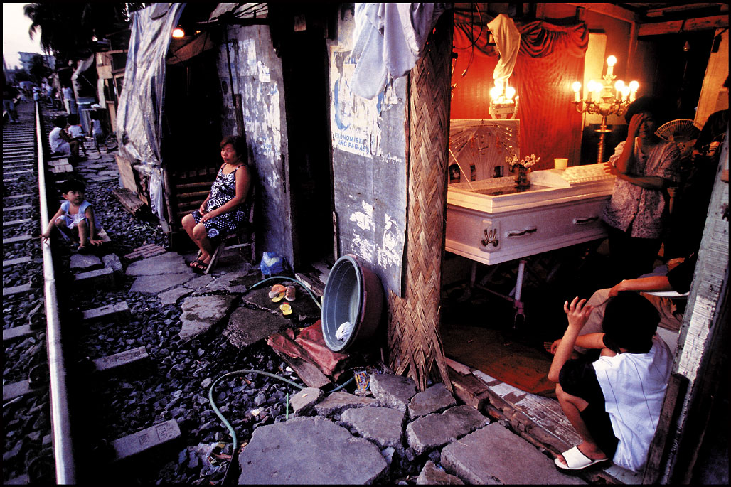 A woman grieves for her husband in her home as life goes on along the main rail line through Manila, Philippines.