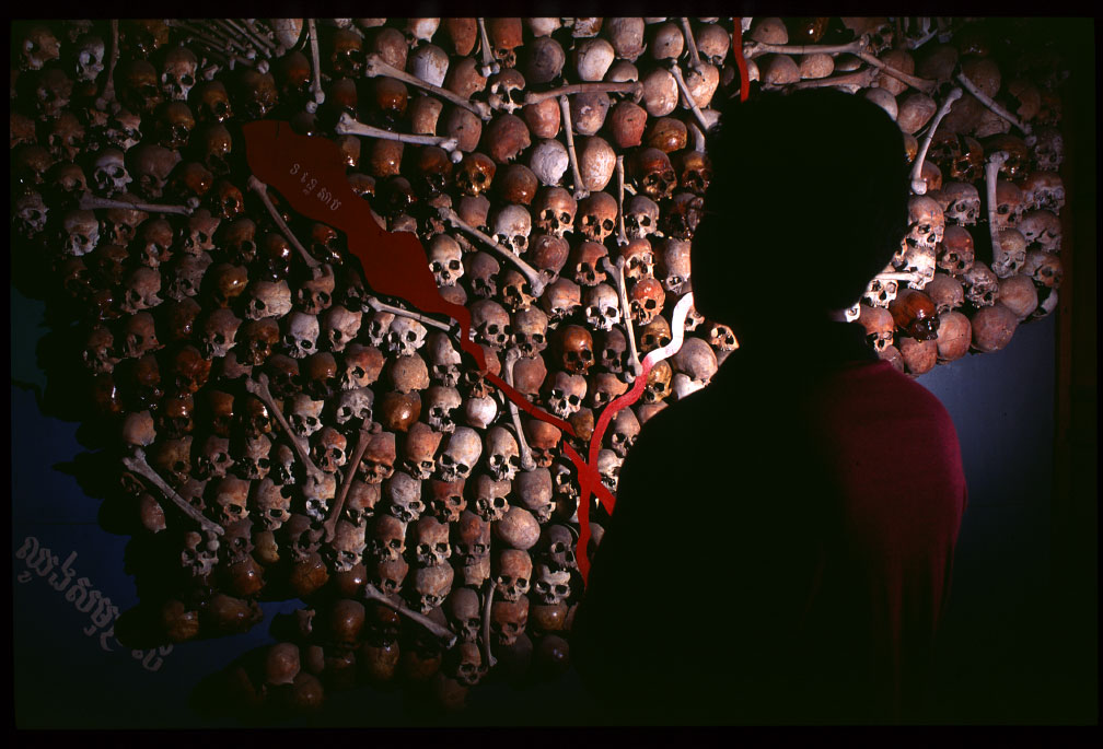A young boy looks at a map of Cambodia made of human skulls in Phnom Penh, Cambodia.