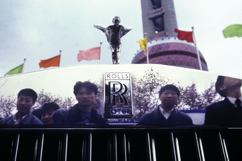 Men are reflected in the front grill of a Rolls Royce in Shanghai, China.