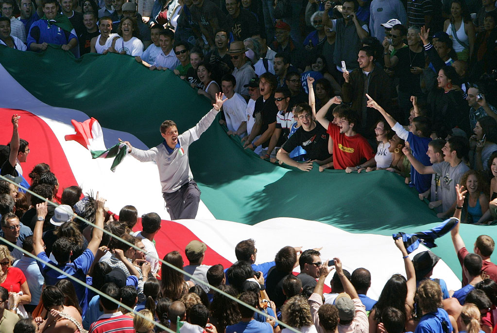 An excited fan jumps on a large Italian flag in north beach after Italy beat France in the world cup.