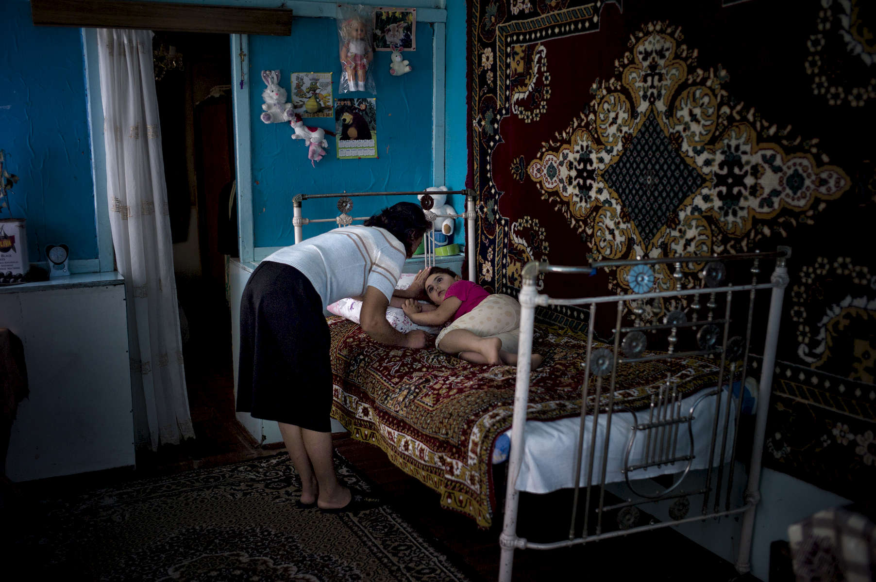 June 04, 2013: MYASNIKYAN, ARMENIA- Anoush Gasparyan watches her five year old sleeping daughter Anahid in their home in the village of Myasnikyan.  The family, which is struggling after a series of accidents and health issues including snake bite and lightning strikes,  receives help from the diaspora-based Children of Armenia Fund (COAF).  COAF was founded by Istanbul-born, American-based Armenian Dr. Garo Armen, who was struck by the depths of poverty in the Aramir region of Armenia and resolved to do something about it.  The organization, which is largely supported by Diasporan Armenians, mostly funds schools, but also assists in providing a more comprehensive social care to the families of the village children. Photo by Scout Tufankjian/Polaris