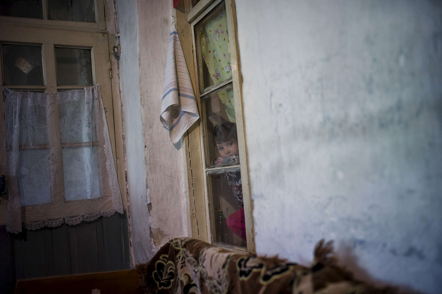 A young girl looks through a window in her home as her father, who lost his leg in a mine accident, talks to visitors in Khtsaberd village.