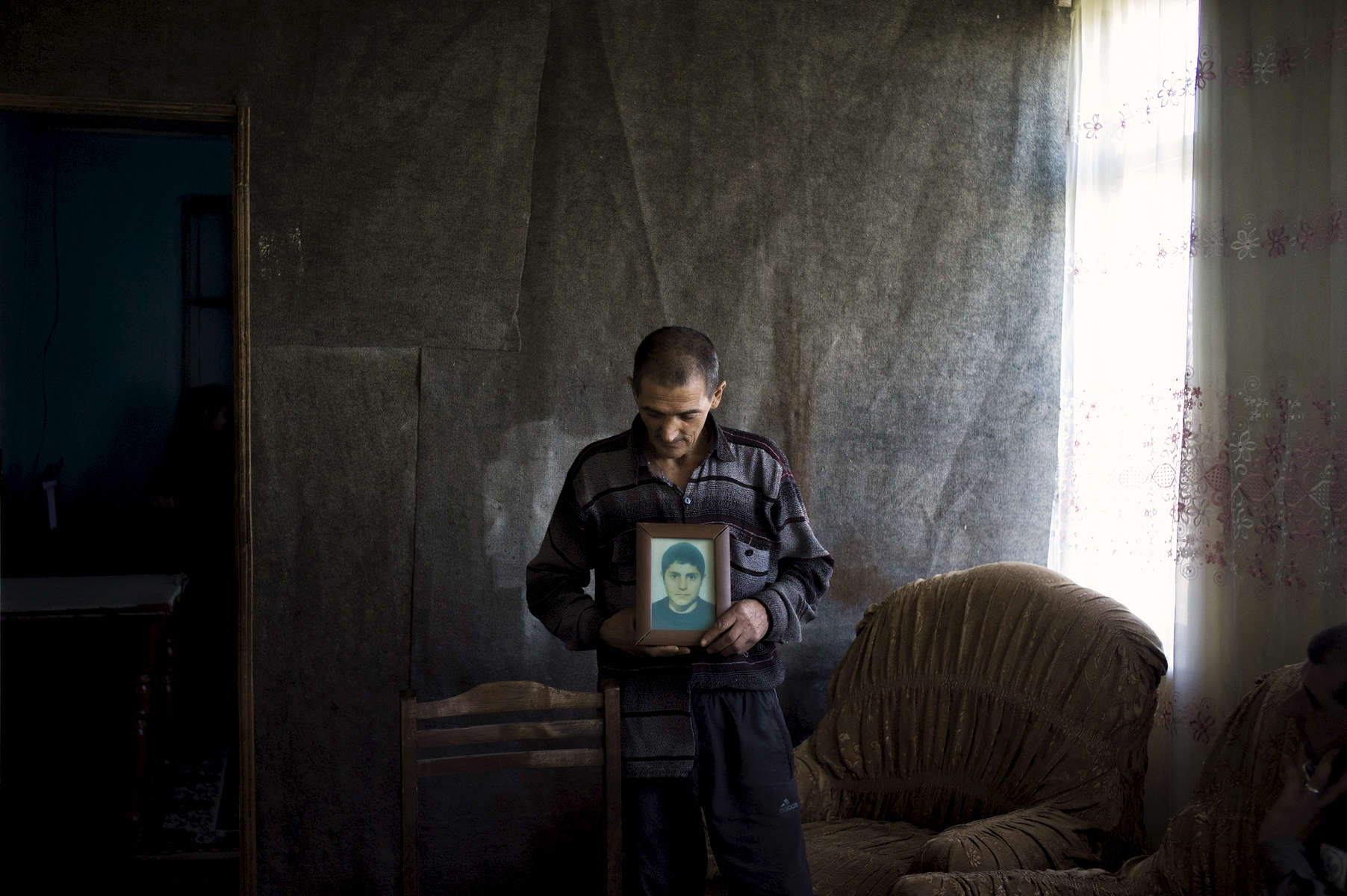 A father holds the portrait of his son who was killed in a cluster bomb accident in Norashen village while gathering scrap metal to help support his family.