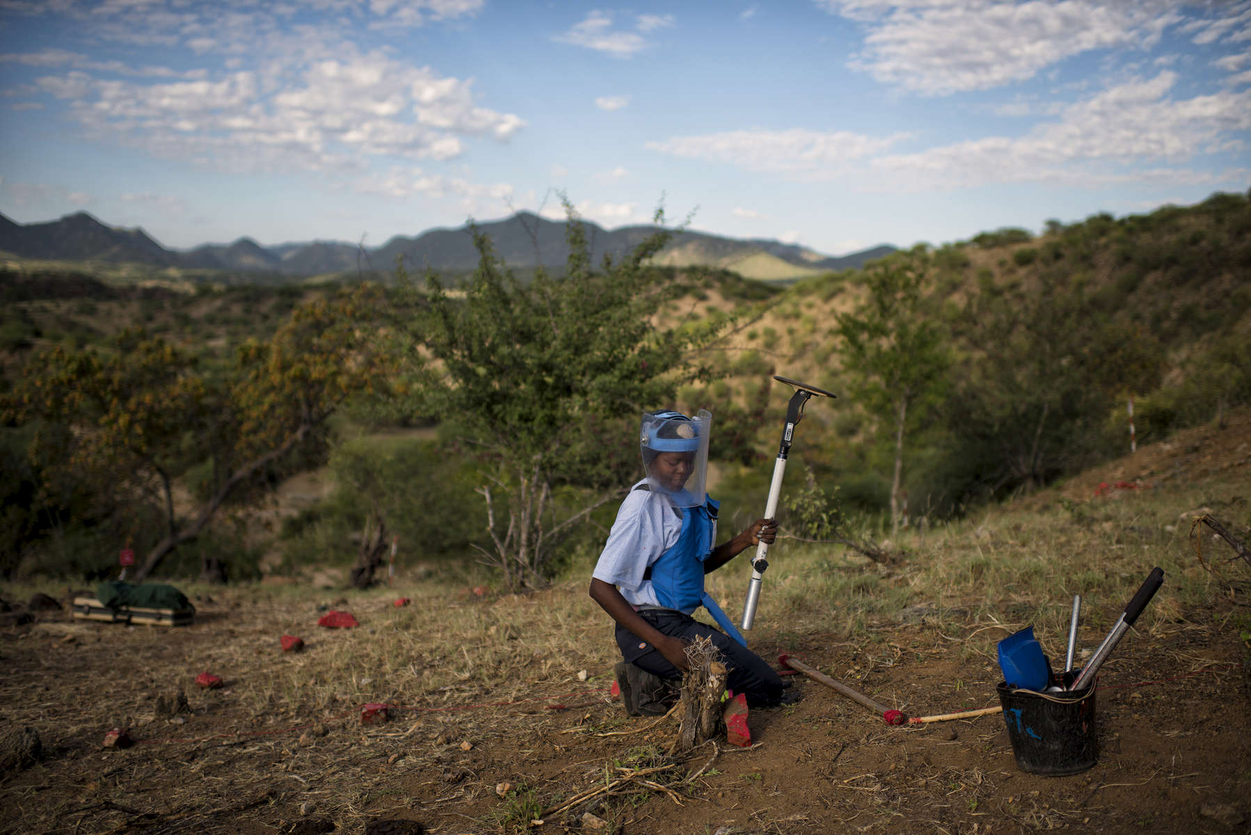 May 3, 2018: KANENGUERERE, ANGOLA - HALO deminer Joana Carlos checks her lane for anti-personnel mines in Kanenguerere.  The area was mined during the civil war by government forces to protect the nearby railway line, as well as various troop positions.