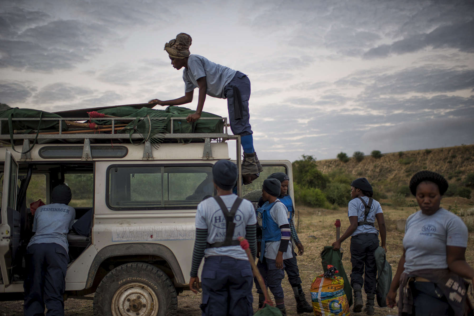 May 4, 2018: KANENGUERERE, ANGOLA - HALO deminer Ana Bimbi Dumbo climbs on the roof of their landrover to start unloading equipment to start their working day in Kanenguerere.  The area was mined during the civil war by government forces to protect the nearby railway line that can be seen in the background, as well as various troop positions. It is currently used by roughly 170 people including village residents and nomadic herders - many of whom are young children - who pass through uncleared land every day.