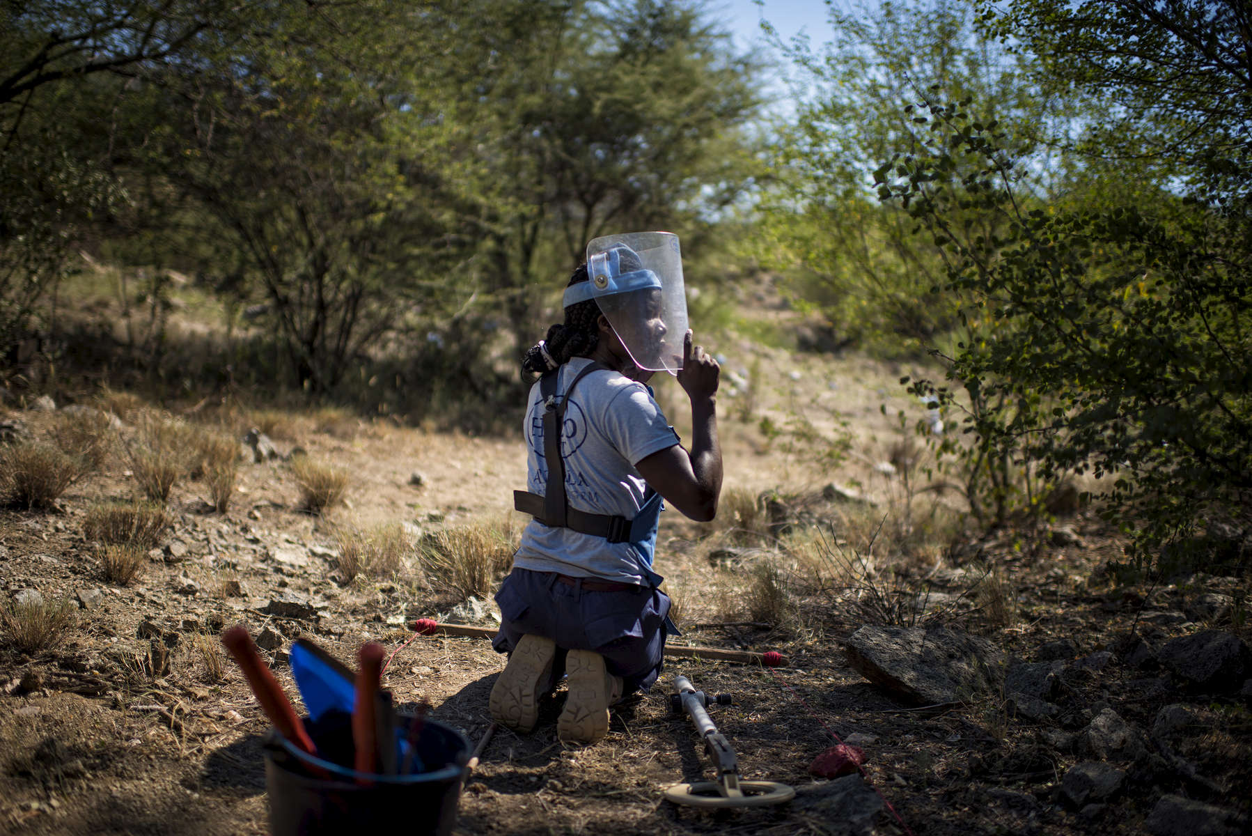 May 3, 2018: KANENGUERERE, ANGOLA - HALO deminer Avelina Cassingue checks her lane for anti-personnel mines in Kanenguerere.  The area was mined during the civil war by government forces to protect the nearby railway line, as well as various troop positions.