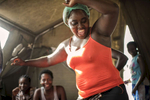 May 3, 2018: KANENGUERERE, ANGOLA - HALO deminer Laurinda Capembe dances in her tent after a full day's  work clearing anti-personnel mines in Kanenguerere.  The area was mined during the civil war by government forces to protect the nearby railway line that can be seen in the background, as well as various troop positions. It is currently used by roughly 170 people including village residents and nomadic herders - many of whom are young children - who pass through uncleared land every day.