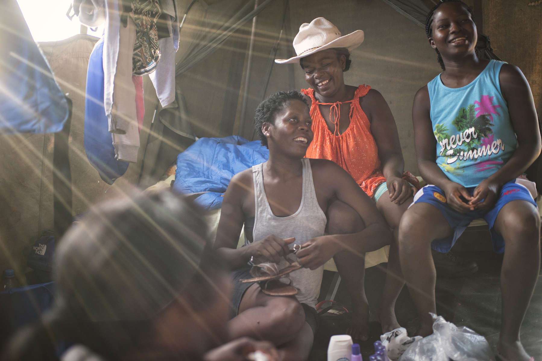 May 3, 2018: KANENGUERERE, ANGOLA - HALO deminers Florida Baptisa (L), Joana Carlos (C), Beatriz Chawayaca, and Cristina Praia relax in their tent after work.  Because the women have limited time off, and most of them have children that the need to spend time with, some of the deminers, including Joana,  take orders for things that the others might want to buy at he camps - everything from fancy underwear and sandals to hair for braiding and perfume to false nails and nail polish, and the women can buy them in the afternoons after a full day's work clearing anti-personnel mines in Kanenguerere.  The area was mined during the civil war by government forces to protect the nearby railway line that can be seen in the background, as well as various troop positions. It is currently used by roughly 170 people including village residents and nomadic herders - many of whom are young children - who pass through uncleared land every day.