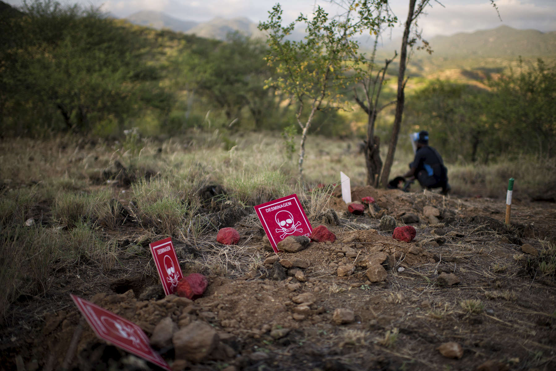 May 4, 2018: KANENGUERERE, ANGOLA - HALO deminer Inês Chipuco works checking for anti-personnel mines in her lane at the top of a hill in Kaneneguerere where she has already found many in a line of laid mines.  These deminers are working in the most difficult field in Kanenguerere.  Not only is extremely hot - with snakes and scorpions common - but the mined area is on the side of an extremely steep hill, making every step dangerous.  The area was mined during the civil war by government forces to protect the nearby railway line that can be seen in the background, as well as various troop positions. It is currently used by roughly 170 people including village residents and nomadic herders - many of whom are young children - who pass through uncleared land every day.