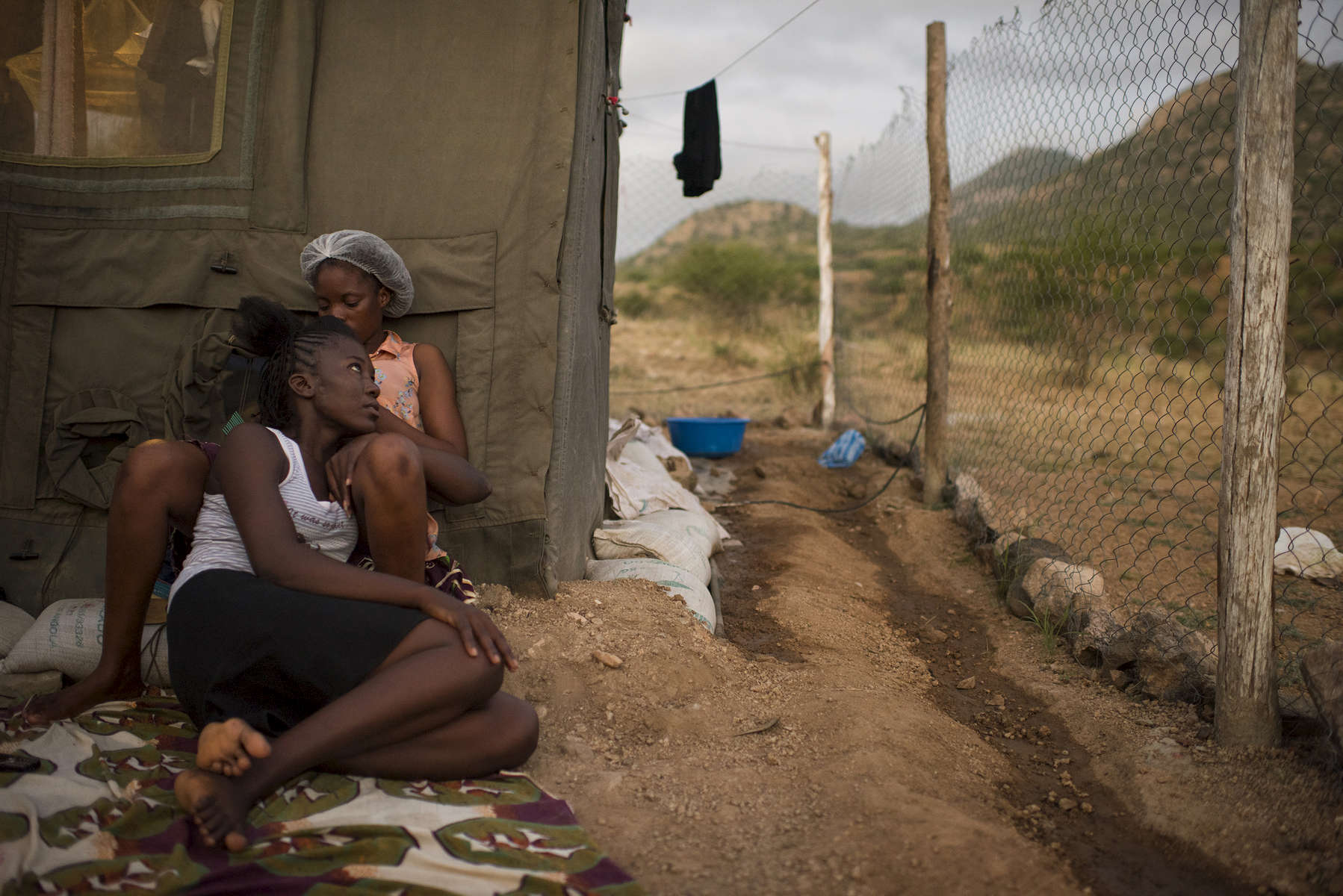 May 4, 2018: KANENGUERERE, ANGOLA -  HALO deminer Domingas Xavier does the hair of her colleague Rita Vambi in front of their tent at the end of the work day.  These deminers are working under extremely difficult circumstances in Kanenguerere.  Not only is extremely hot - with snakes and scorpions common - but much of the mined area is on the side of an extremely steep hill, making every step dangerous.  As a result, afternoons are often spent making themselves look and feel fantastic. The area was mined during the civil war by government forces to protect the nearby railway line that can be seen in the background, as well as various troop positions. It is currently used by roughly 170 people including village residents and nomadic herders - many of whom are young children - who pass through uncleared land every day.